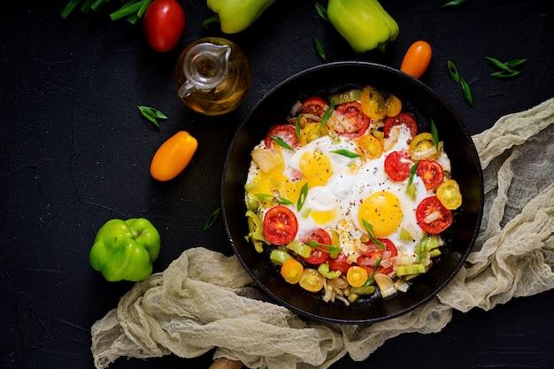 Huevos fritos con verduras - shakshuka en una sartén sobre un fondo negro. endecha plana. vista superior