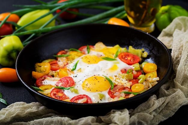 Huevos fritos con verduras - shakshuka en una sartén sobre un fondo negro