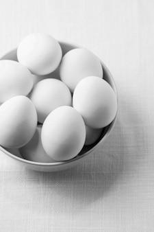 Huevos de gallina blanca de alto ángulo en un tazón