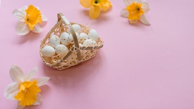 Huevos de gallina blanca en canasta con flores brillantes