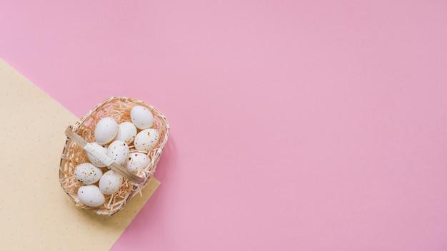 Huevos de gallina blanca en canasta en mesa rosa