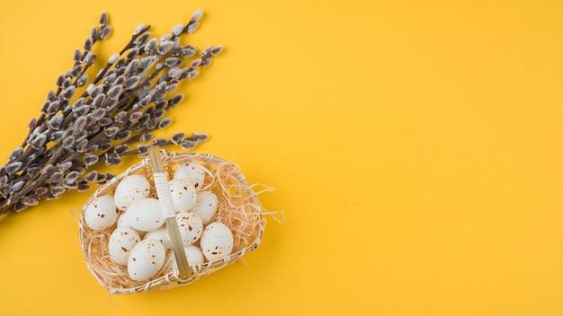 Huevos de gallina blanca en canasta con ramas de sauce