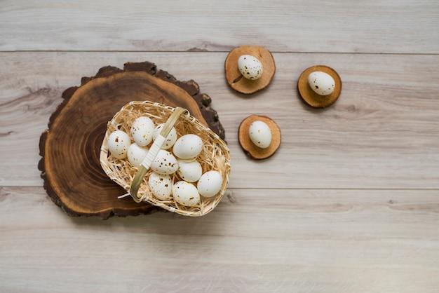 Huevos de gallina blanca en canasta sobre tabla de madera