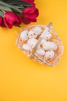 Huevos de gallina blanca en canasta con tulipanes rojos