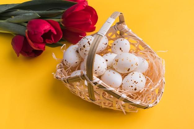 Huevos de gallina blanca en canasta con tulipanes