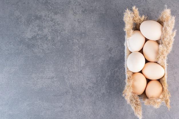 Huevos de gallina blanca cruda fresca con espigas colocadas sobre la mesa de piedra.