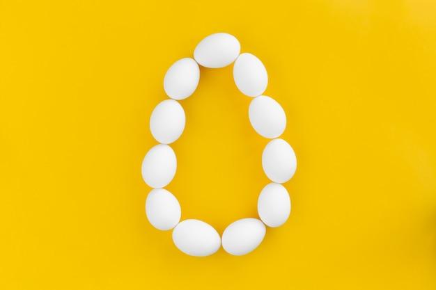 Huevos de gallina blanca se encuentran en la forma de un huevo grande en amarillo