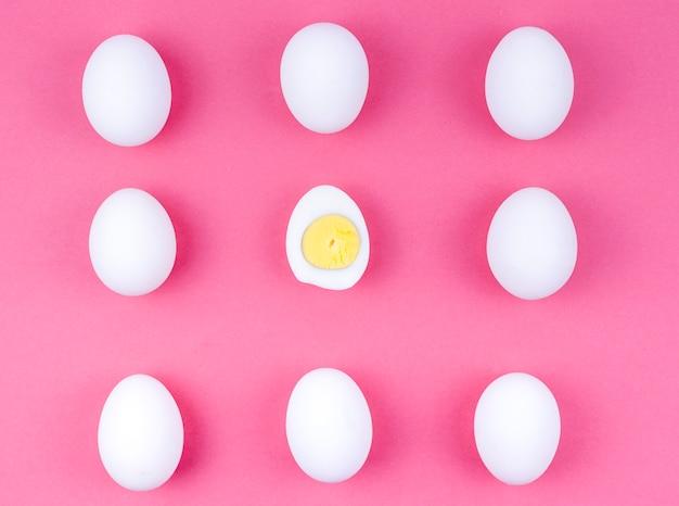 Huevos de gallina blanca con huevo cocido en mesa