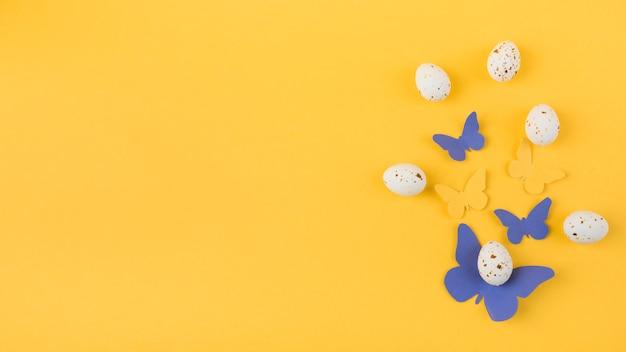Huevos de gallina blanca con mariposas de papel.