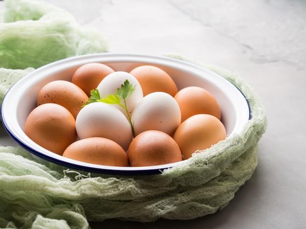 Huevos de gallina blanca y marrón en un tazón sobre hormigón gris
