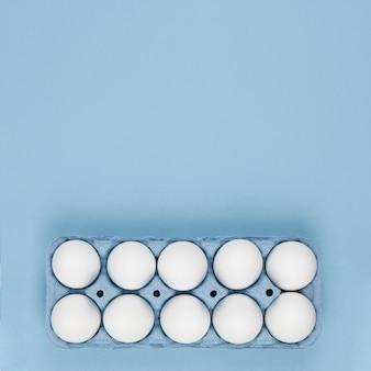 Huevos de gallina blanca en rejilla en mesa