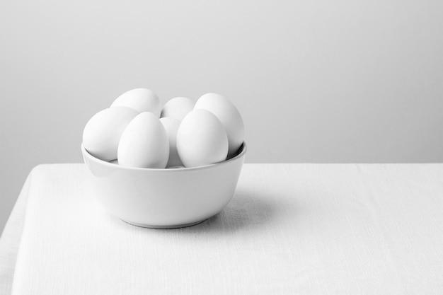 Huevos de gallina blanca vista frontal en un tazón con espacio de copia