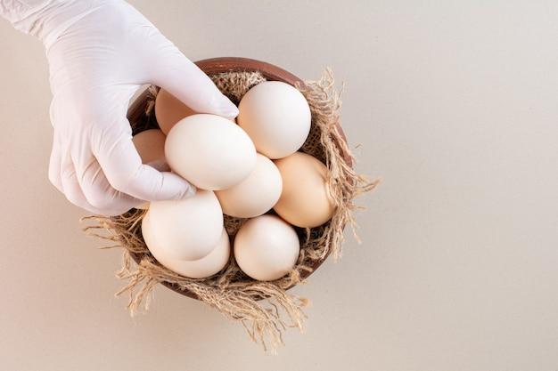 Huevos de gallina blancos crudos frescos colocados en mesa beige.