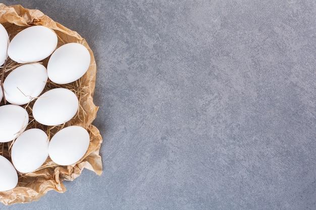 Huevos de gallina blancos crudos frescos colocados sobre la mesa de piedra.