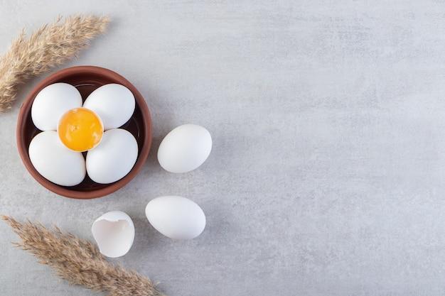 Huevos de gallina blancos frescos crudos colocados sobre un fondo de piedra.