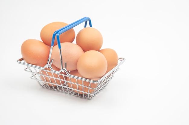 Huevos de gallina en una canasta de supermercado sobre un fondo blanco.