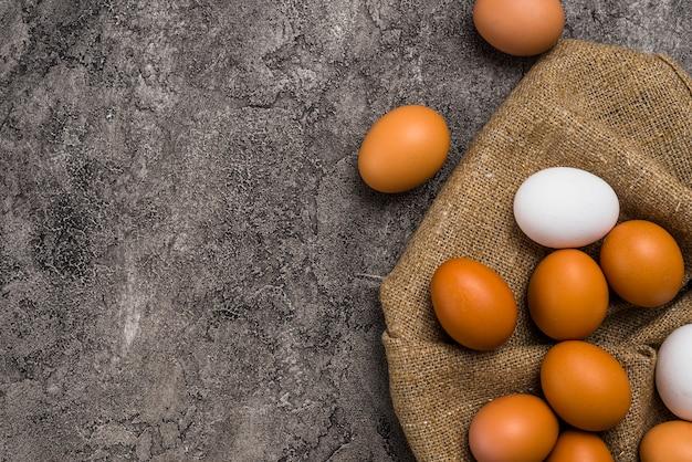 Huevos de gallina esparcidos sobre tela marrón.