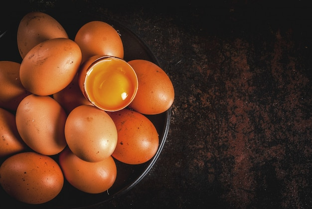 Huevos de gallina de granja orgánica, en un plato, sobre un metal oxidado oscuro, vista superior