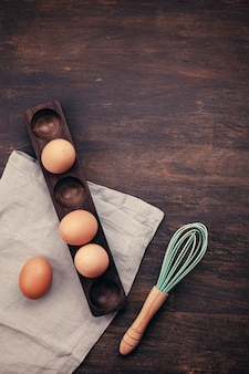 Huevos de gallina marrón en el soporte de madera sobre el fondo rústico