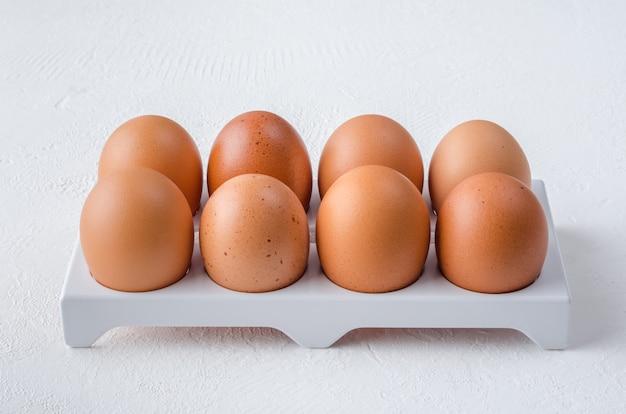 Huevos de gallina roja en la bandeja de la nevera.