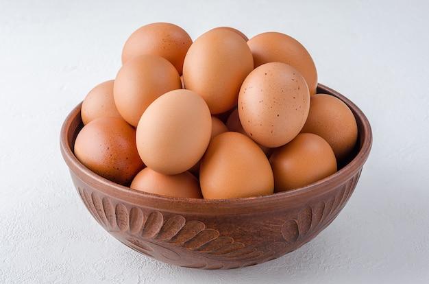Huevos de gallina roja en un recipiente de arcilla