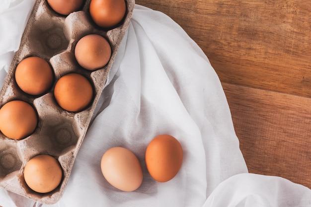 Huevos de gallina en tela blanca sobre mesa de madera, vista superior
