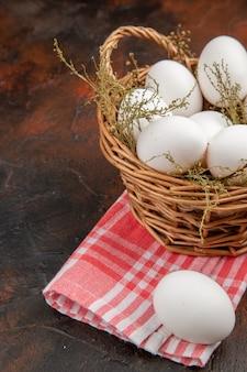 Huevos de gallina vista frontal dentro de la canasta sobre la superficie oscura