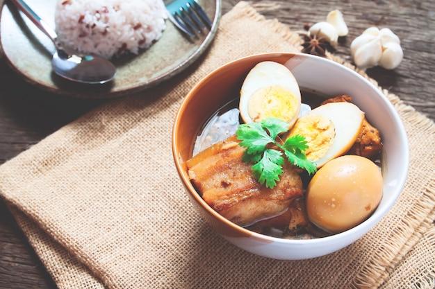 Huevos guisados y carne de cerdo o huevos y carne de cerdo en salsa marrón en un tazón con especias en mesa de madera