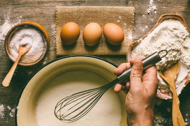 Huevos, harina y una mano masculina con un batidor de masa.