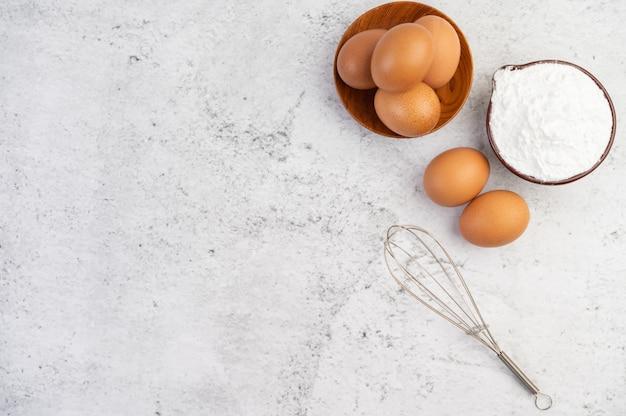 Huevos, harina de tapioca en una taza y batidor de huevos.