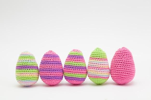 Huevos hechos punto de la decoración de pascua en un fondo blanco. hecho a mano, amigurumi