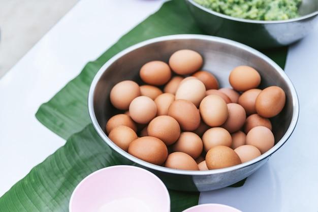 Los huevos hervidos en cuenco inoxidable en plátano se van en la tabla.
