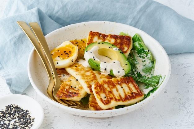 Huevos hervidos suaves de la dieta de keto ketogenic con el aguacate y la lechuga en el primer en colores pastel del fondo