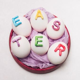 Huevos con letras de pascua en bandeja