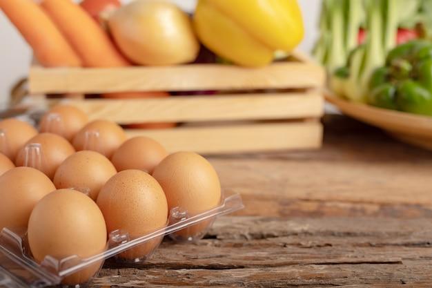 Huevos en la mesa de madera y vegetales en una caja de madera