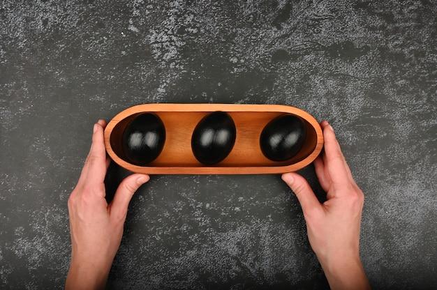 Huevos negros en las manos. aplanada pascua negra tres huevos negros