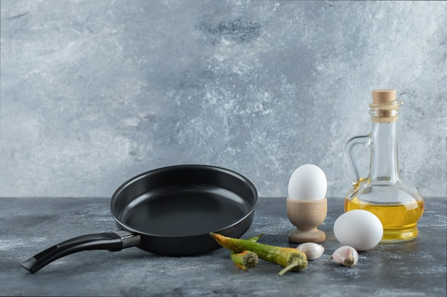 Huevos orgánicos frescos con pimienta y aceite sobre fondo gris