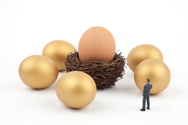 Huevos de oro y hombre de negocios sobre fondo blanco.