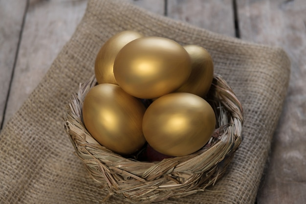 Huevos de oro en el nido en la mesa de madera vintage oscura
