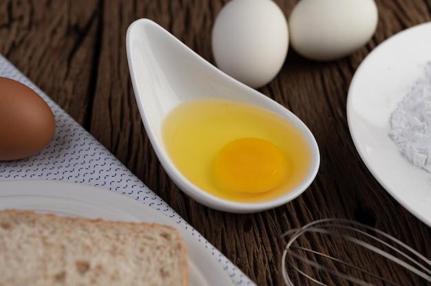 Huevos, pan, harina de tapioca y un batidor de huevo, ingredientes utilizados en panadería.
