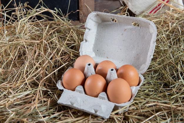 Huevos en el paquete en la paja
