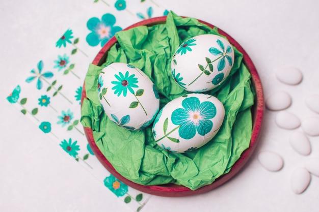Huevos de pascua con adornos florales colocados en bandeja