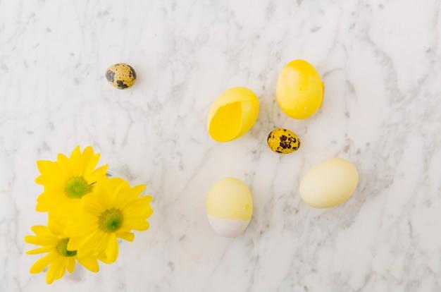 Huevos de pascua amarillos cerca de flores frescas