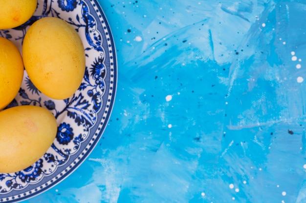 Huevos de pascua amarillos en placa en la mesa
