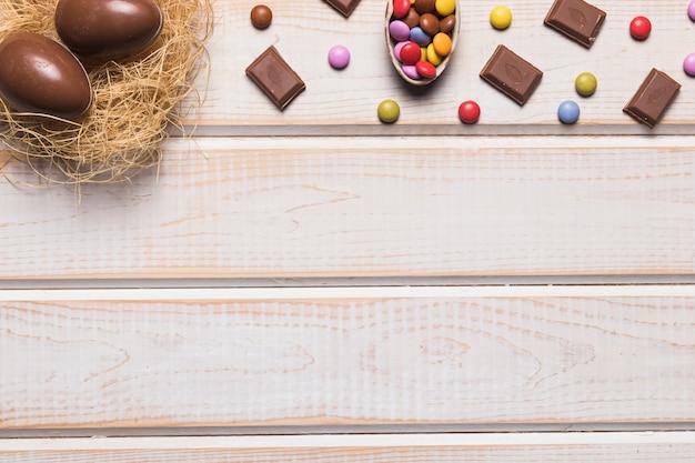 Huevos de pascua anidan; chocolates y gemas en escritorio de madera con espacio para escribir el texto.