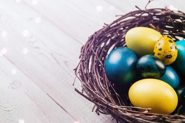 Los huevos de pascua azules y amarillos en un nido de pájaro en una mesa de madera blanca copian el espacio.