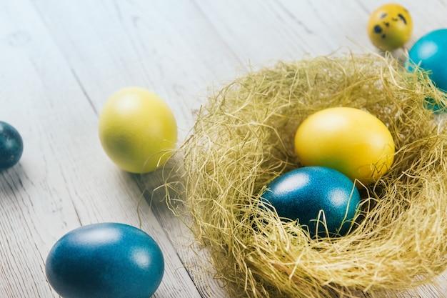 Los huevos de pascua azules y amarillos en un nido de sisal en un espacio de copia de mesa de madera blanca.