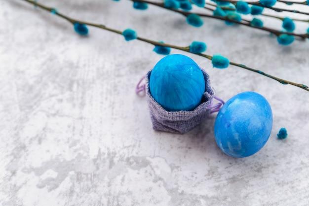 Huevos de pascua azules con bolsa decorativa y ramitas de sauce.