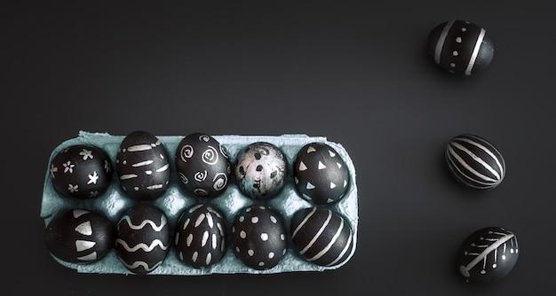 Huevos de pascua en bandeja en mesa aislada negro