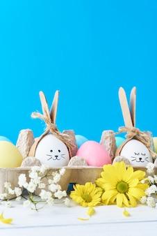 Huevos de pascua en bandeja de papel con decoración sobre un fondo azul.